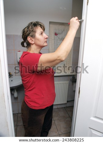 Woman paint doors in white color, looking up - stock photo