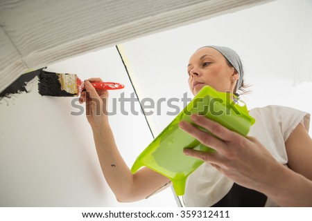 Woman paint wall at home.  - stock photo