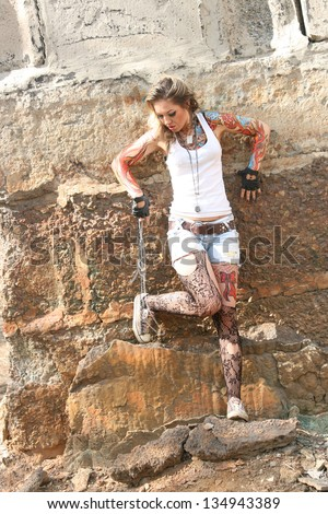 woman painted body art in the form of fire in the t-shirt and denim shorts and torn pantyhose on the background of the industrial buildings of reinforced concrete slabs