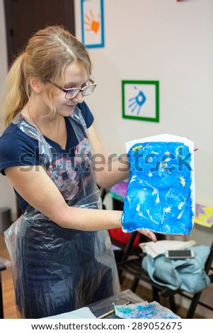 Woman painter holding silk with printing from water ebru drawing - stock photo