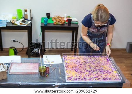 Woman painter making pattern on water surface with inks and stick - stock photo
