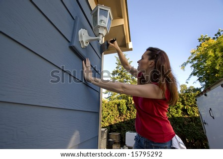 Woman Painting a House with blue paint. Horizontally framed photo. - stock photo