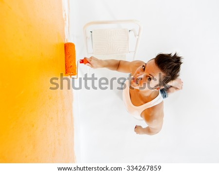Woman painting a wall seen from above. - stock photo