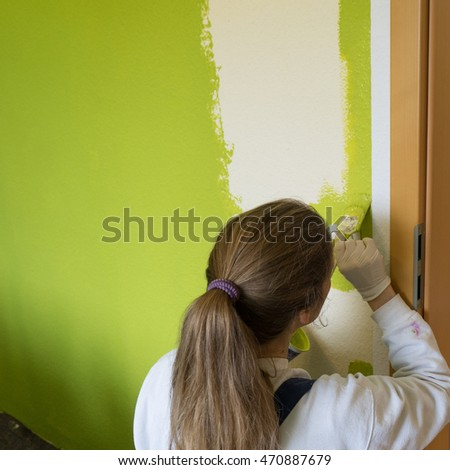 woman painting a wall with green paint / painters / wall color