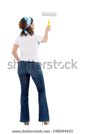 Woman painting a white wall and redecorating her house - isolated  - stock photo