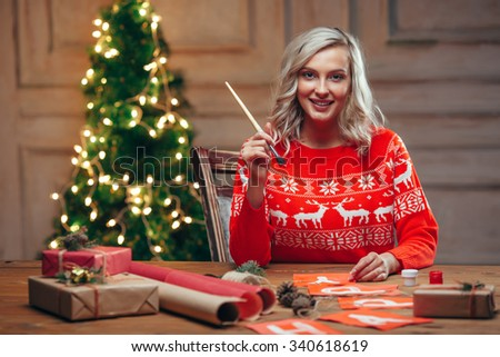 woman painting christmas flags with brush looking at camera, rustic style - stock photo
