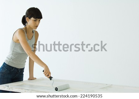 Woman painting door with paint roller - stock photo