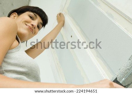 Woman painting door with paint roller, smiling at camera, low angle view - stock photo