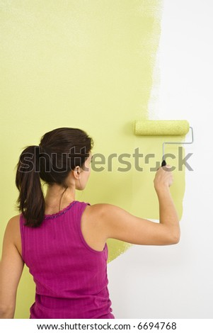 Woman painting interior wall of home with paint roller.