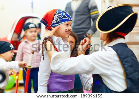 woman painting kid's face on party - stock photo