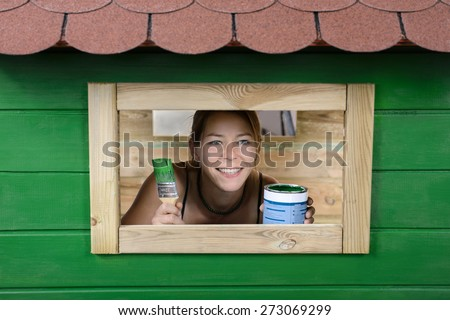 Woman painting small house - stock photo