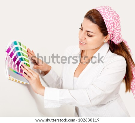 Woman painting the wall and holding a color guide - stock photo
