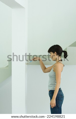 Woman painting wall with paint brush - stock photo