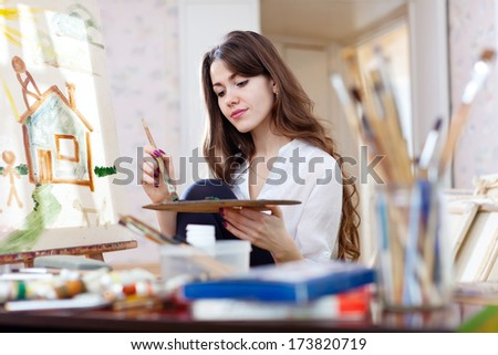 Woman paints home of dreams on canvas in workshop - stock photo