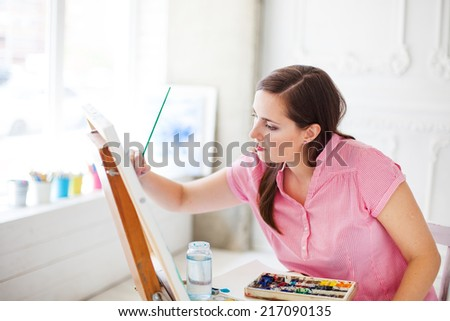 woman paints picture on canvas in her white studio - stock photo