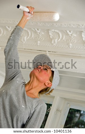 Woman paints the ceiling - stock photo