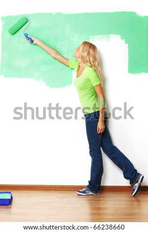 woman paints the wall - stock photo