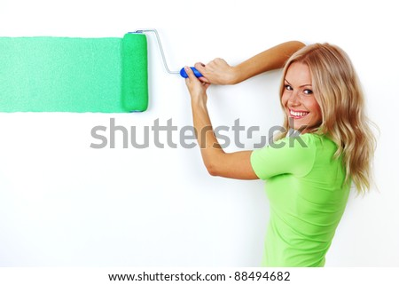 woman paints the wall brush