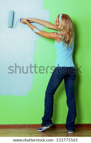 woman paints the wall roller - stock photo