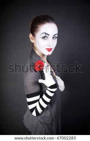 Woman pantomime with a red flower on a black background - stock photo
