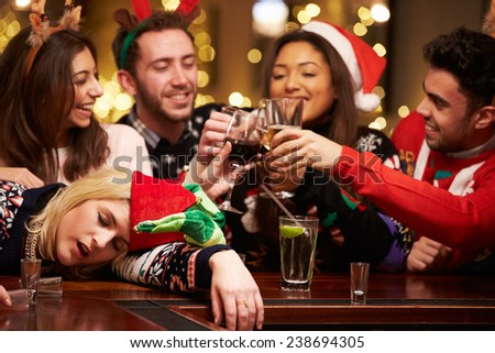 Woman Passed Out On Bar During Christmas Drinks With Friends - stock photo