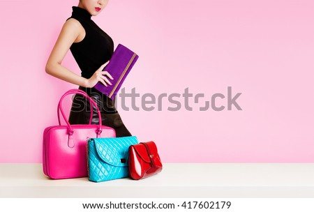 Woman passing in front of many bags and purses. shopping. fashion image. isolated on pink background.  - stock photo