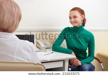woman patient at doctor's consultation in clinic - stock photo