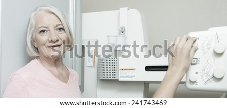 Woman patient ready to be scanned at X-Ray machine. - stock photo