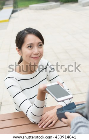 Woman pay with cellphone by NFC