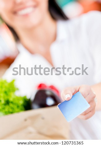 Woman paying by credit card at the supermarket - stock photo