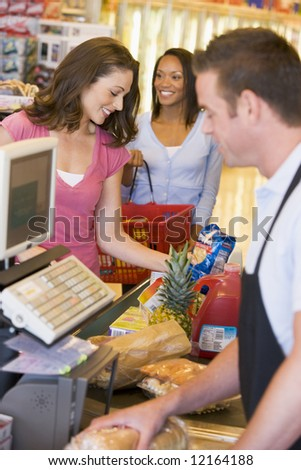 Woman paying for groceries at supermarket checkout - stock photo