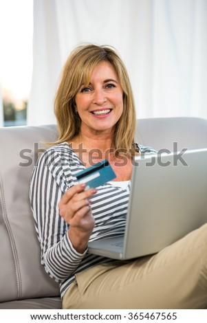 Woman paying on internet with her credit card - stock photo