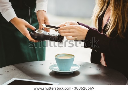 Woman paying with mobile phone in cafe - stock photo