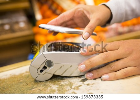 Woman paying with nfc technology on mobile phone in supermarket, electronic reader  - stock photo