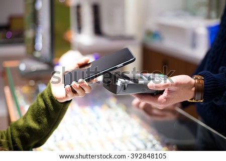 Woman paying with NFC technology on smart phone at shop - stock photo