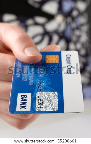 Woman pays a bill with credit card.Focus on foreground. - stock photo