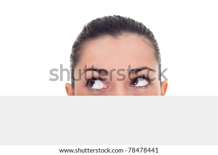 woman peeking hidden over blank billboard and looking in side,  isolated on white background - stock photo