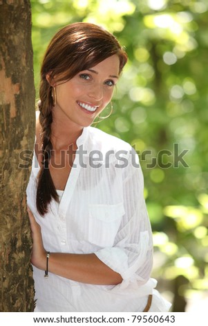 Woman peeking out from behind a tree - stock photo