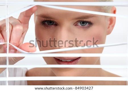 Woman peeking through some blinds - stock photo