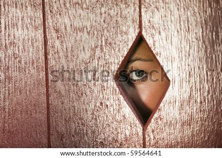 Woman peeks through a diamond shaped hole in a wall. Horizontal shot. - stock photo