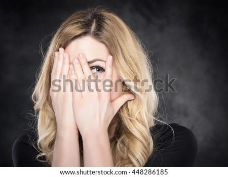 Woman peeping through her fingers.  - stock photo