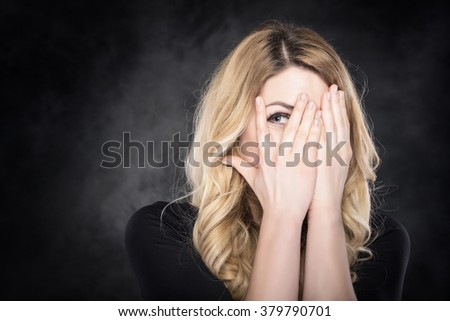 Woman peeping through her fingers over dark background - stock photo