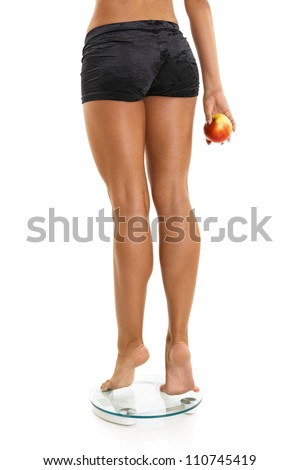 Woman perfect shaped legs on scale with red apple in hand.Isolated on white. - stock photo
