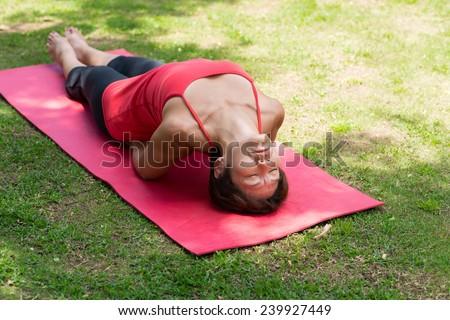 Woman performing fish yoga position - stock photo