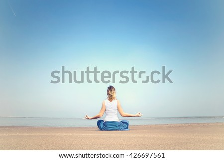 woman performing relaxation and meditation exercises at the sea - stock photo