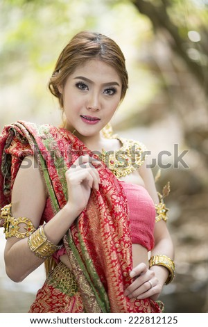 woman performing typical thai dance with thai style nature background, identity culture of thailand - stock photo