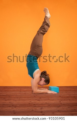 Woman performs Feathered Peacock Yoga Pose over orange background - stock photo