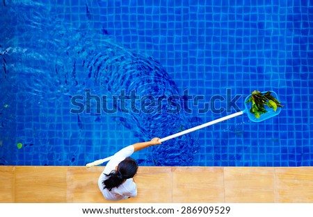 woman, personnel cleaning the pool from leaves - stock photo