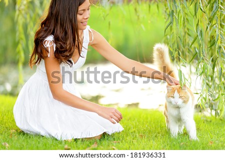 Woman petting cat in summer park. Happy cute girl playing with adorable cats in city park during spring or summer. Beautiful mixed race Asian Caucasian female model smiling happy outdoors. - stock photo