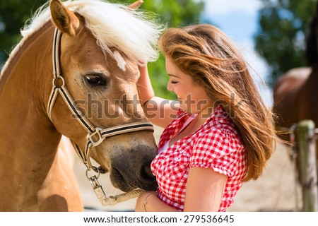 Woman petting horse on pony farm - stock photo